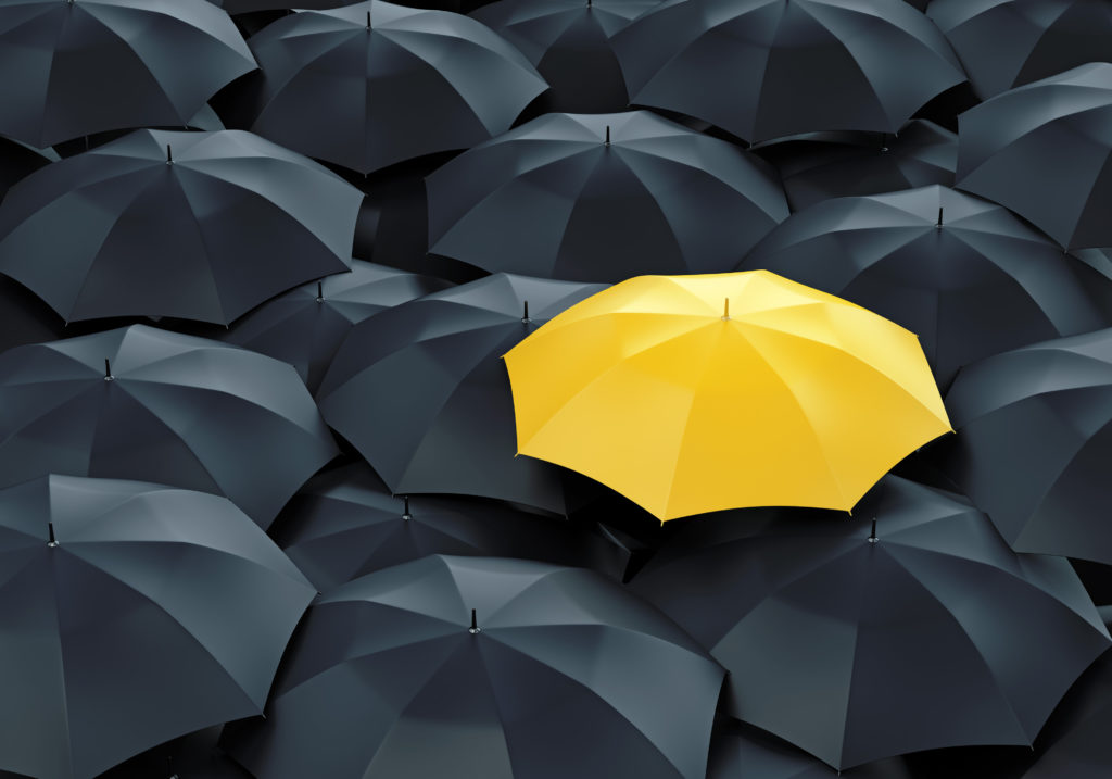 Overhead view of one open, yellow umbrella surrounded by open, black umbrellas, illustrating differentiation as growth strategy.